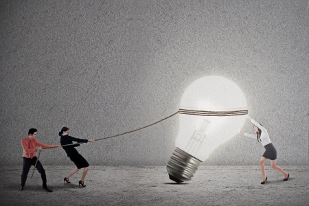 Business teamwork is pulling a bright light bulb on grey background photo