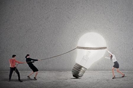 innovacion: Negocios trabajo en equipo est� tirando de una bombilla de luz brillante sobre fondo gris