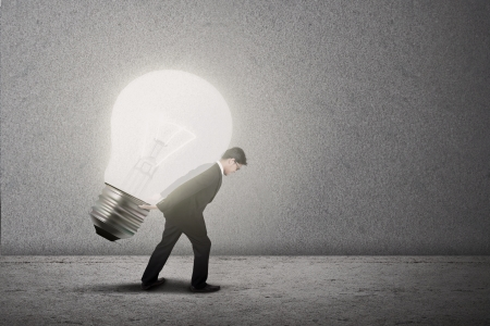 Businessman is carrying a bright light bulb