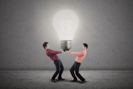 Two businessmen are holding a bright light bulb photo