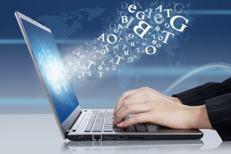 Female hands typing on the laptop with flying letters  Stock Photo