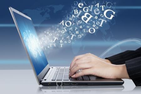 języki: Kobieta rÄ™ce wpisujÄ…c na laptopie z literami latajÄ…cych