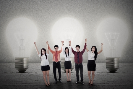 Concept of a successful team with bright idea on light bulbs background photo