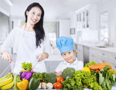 family kitchen: Mother and son are making healthy salad at home