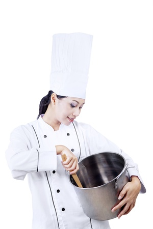 stirring: Beautiful chef is stirring chocolate inside a pan on white background