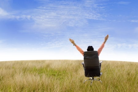 the concept of independence: Businessman raising his hands while sitting on his seat in the field under blue sky