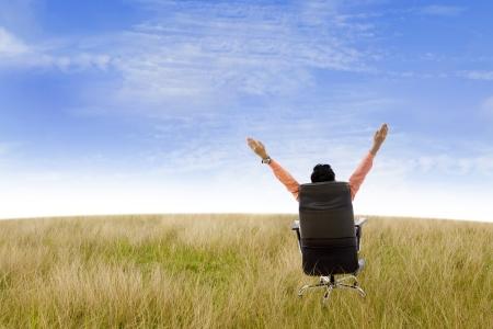 independencia: Hombre de negocios levantando las manos mientras est� sentado en su asiento en el campo bajo el cielo azul