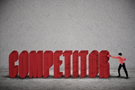 Businessman is punching the word COMPETITOR on grey background photo