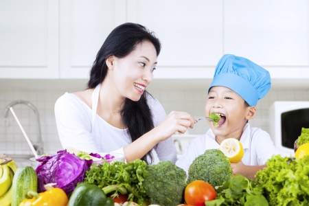 brocoli: Mother feed brocolli to her child in the kitchen
