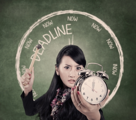 running out of time: Angry business woman smashing an alarm clock by using hammer
