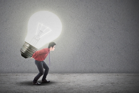 Asian businessman is carrying bright light bulb on grey background Stock Photo - 18936759
