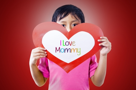 Boy is holding a love card for his mommy photo