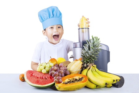 Little chef boy making healthy fruit juice with electric juicer on white background photo