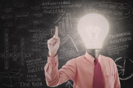 Bright businessman has idea with written blackboard as background Stock Photo - 18936760