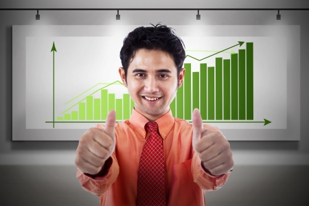 Businessman with thumbs up on profit bar chart background photo