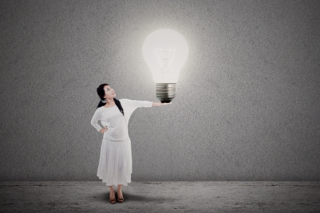 Young entrepreneur holding a bright light bulb  idea  on grey background photo