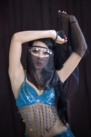 buikdansen: Aantrekkelijke Aziatische buikdansen op zwarte achtergrond Stockfoto