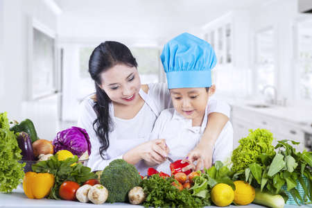Young mother teach her son to cut vegetables at home photo