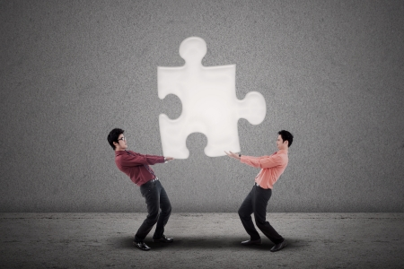 Two businessmen carry a puzzle together on grey background photo