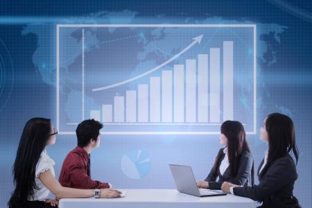 business asia: Business team guardando grafico a barre profitto sul touchscreen