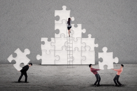 PARTNER: Business team building puzzles together on grey background Stock Photo