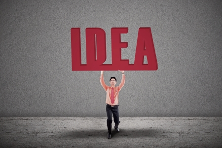 Businessman is holding the word Idea on grey background Stock Photo - 18960847