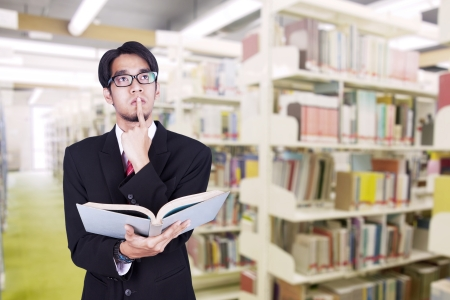 Businessman is contemplating while holding book in a library photo