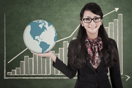 Businesswoman holds a globe with profit bar chart background photo