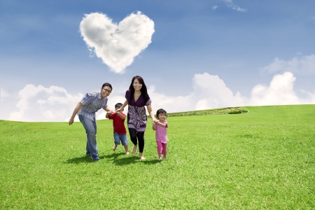 heart under: Happy family is running together in the park under heart shape clouds