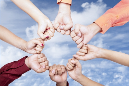 creative strength: Close up of hands gesturing unity under blue sky