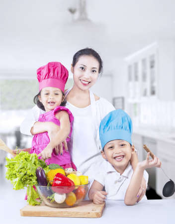 Happy family with fresh vegetable at home photo