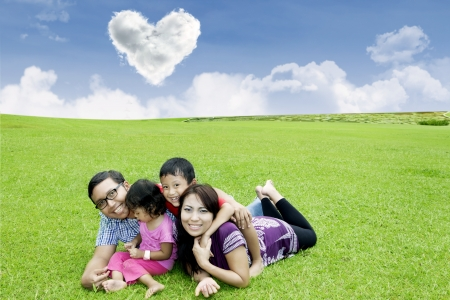 under heart: Happy family is laying down on the grass field under heart shape clouds