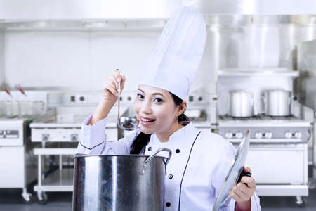 pan asian: Asian chef is tasting a traditional soup in the kitchen Stock Photo