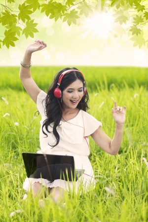 Beautiful girl listening to music with headphone and laptop in the park photo