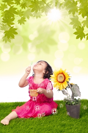 Little girl is blowing bubbles and sunflower photo