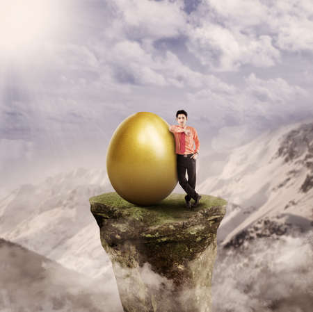 Businessman has golden egg on top of a mountain rock photo