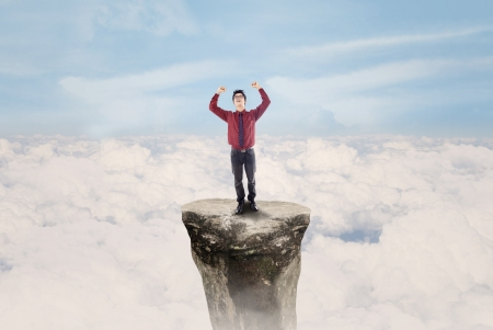 Businessman raised his arms on top of a rock, above clouds photo