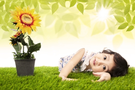 asian children: Cute girl laying on the ground with sunflower