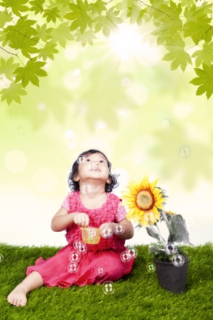 Little girl blowing bubbles under the sun photo