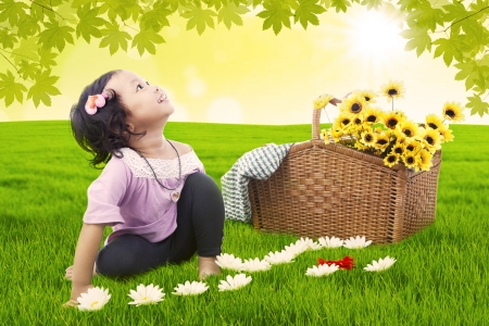 child looking up: Little girl having picnic with flower basket Stock Photo