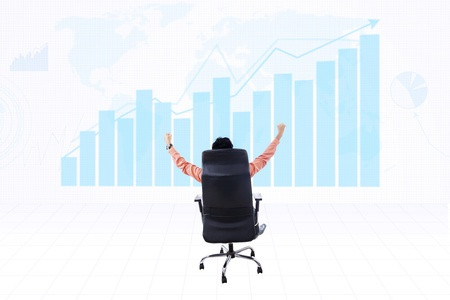 Businessman raising his arms with profit bar chart background photo
