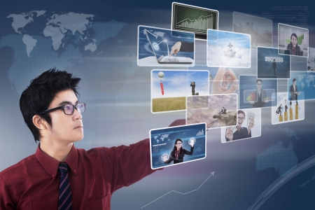 Businessman choosing photos on touchscreen with world map background photo