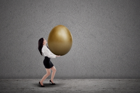 Asian businesswoman is carrying golden egg on grey background photo