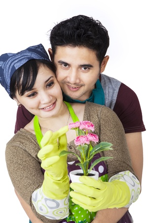 Asian coule is holding a plant on white background photo