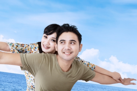 flying man: Asian couple pretends to fly together under blue sky