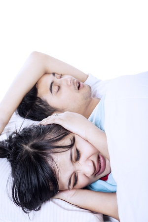 Wife closed her ears due to annoying sound of her husband snore photo