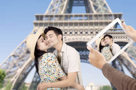 Asian couple took picture at eiffel tower in Paris with e-tablet photo
