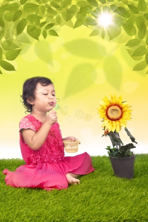 Little girl blowing bubbles in the garden photo