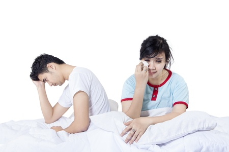 chinese sex: Young couple had a fight in bed on white background Stock Photo