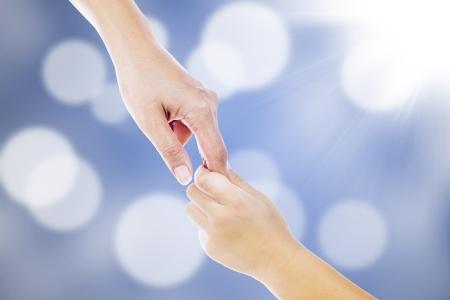 ayudando: Gestos de las manos de la madre para ayudar a un ni�o en desenfocado luces azules